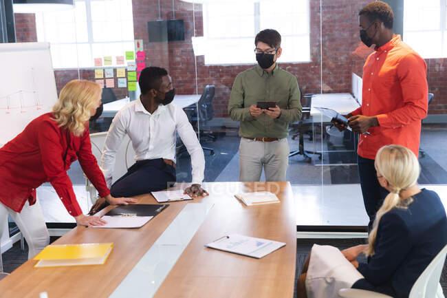 Група різних колег по офісу - чоловіків і жінок у масках, які обговорюють питання в офісі. гігієна і соціальна дистерія на робочому місці під час 19 пандемії. — стокове фото