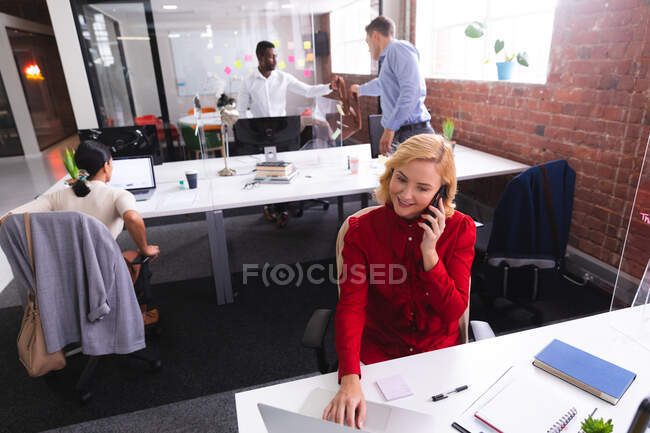Caucasian woman talking on smartphone while using laptop sitting on her desk at modern office. business, professionalism and office concept — Stock Photo