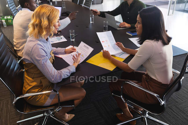 Two diverse female office colleagues discussing over document in meeting room at office. business, professionalism, office and teamwork concept — Stock Photo