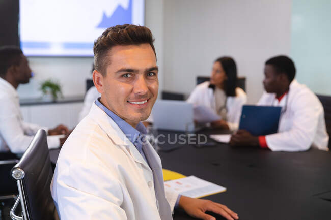 Portrait of caucasian male doctor smiling while sitting on a chair in meeting room. healthcare and professionalism concept — Stock Photo