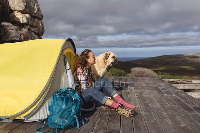 Felice donna caucasica campeggio con cane da compagnia, seduto fuori tenda sul ponte di montagna. una vita sana, fuori dalla griglia e vicino alla natura. — Foto stock