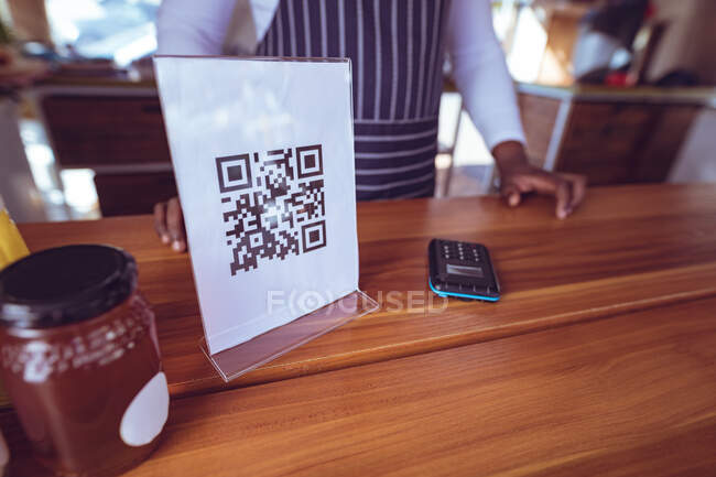Midsection of african american man in food truck with qr code menu on worktop. independent business and street food service concept. — Stock Photo