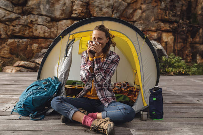 Happy caucasian woman camping, sitting drinking coffee outside tent on mountainside deck. healthy living, off the grid and close to nature. — Stock Photo