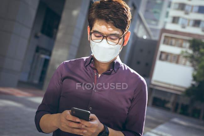 Homem de negócios asiático usando máscara facial usando smartphone na rua da cidade. nômade digital para fora e sobre na cidade durante covid 19 conceito pandêmico. — Fotografia de Stock