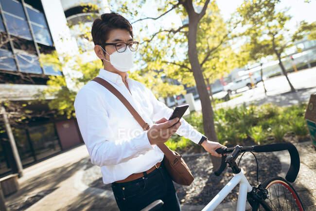 Азіатський бізнесмен, одягнений в маску обличчя за допомогою смартфона, який тримає велосипед на міській вулиці. Цифровий кочівник і все в місті під час кочівлі 19 пандемії. — стокове фото