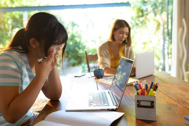 Asiatique fille à l'aide d'un ordinateur portable, apprendre en ligne sa mère travaillant en arrière-plan. à domicile en isolement pendant le confinement en quarantaine. — Photo de stock