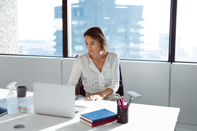 Caucasian businesswoman sitting at desk, using laptop at work. independent creative business at a modern office. — Stock Photo
