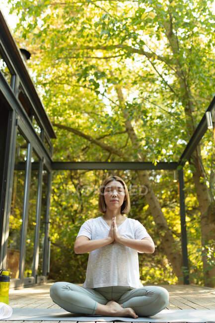 Азиатка практикует йогу с закрытыми глазами на террасе в саду. в доме в изоляции во время карантинной изоляции. — стоковое фото