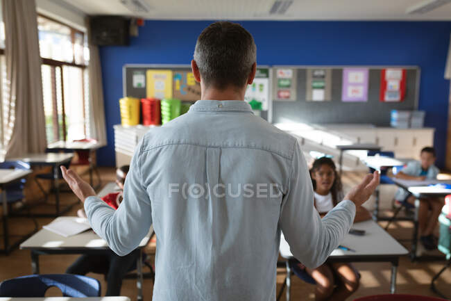 Vista trasera de la enseñanza de maestros caucásicos masculinos a diversos estudiantes de la clase en la escuela primaria. escuela y concepto de educación - foto de stock