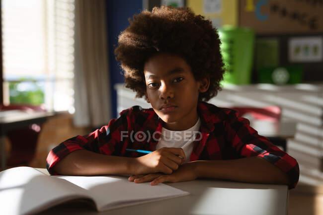 Portrait d'un garçon afro-américain assis sur son bureau en classe à l'école primaire. concept scolaire et éducatif — Photo de stock