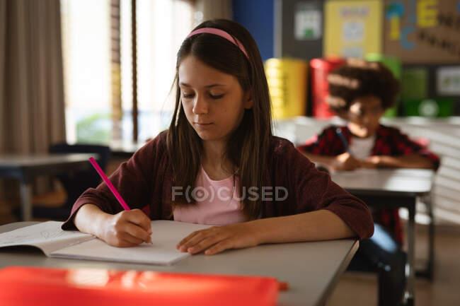 Femme caucasienne étudiant tout en étant assis sur son bureau en classe à l'école primaire. concept scolaire et éducatif — Photo de stock
