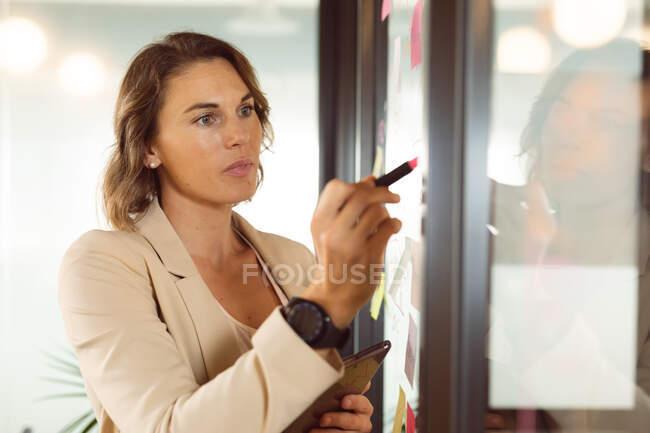 Кавказька бізнес-леді робить нотатки і додає постін на прозорій дошці. Незалежний творчий бізнес у сучасному офісі.. — стокове фото