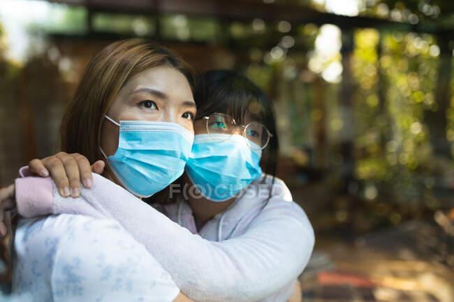 Triste mujer asiática y su hija abrazando el uso de máscaras faciales y mirando por la ventana. en casa en aislamiento durante la pandemia covid 19 y el bloqueo de cuarentena. - foto de stock
