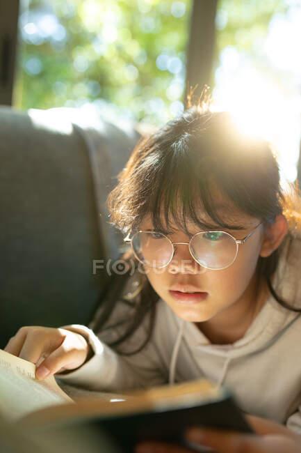 Азійська дівчинка в окулярах читає книжку і лежить на дивані. вдома в ізоляції під час карантину.. — стокове фото