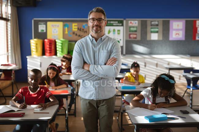 Портрет вчителя чоловічої статі з руками перехрестився в класі в початковій школі. школа і освіта — стокове фото