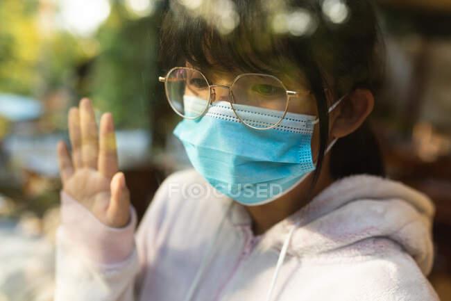 Triste chica asiática en gafas con máscara facial y mirando por la ventana. en casa en aislamiento durante la pandemia covid 19 y el bloqueo de cuarentena. - foto de stock