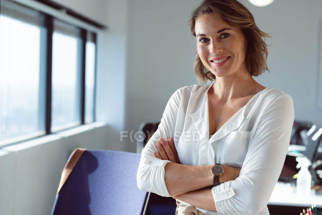Smiling caucasian businesswoman standing with arms crossed at work. independent creative business at a modern office. — Stock Photo