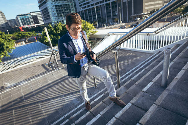 Asian businessman talking on smartphone walking up steps in city street. digital nomad out and about in city concept. — Stock Photo