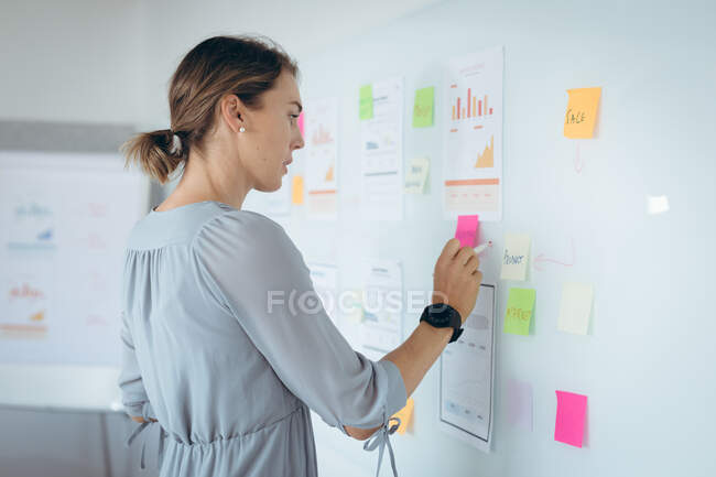 Caucasian businesswoman making notes and add post-ins on wall. independent creative business at a modern office. — Stock Photo