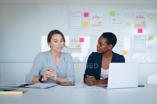 Deux femmes d'affaires diverses assises au bureau, utilisant un ordinateur portable, parlant. entreprise créative indépendante dans un bureau moderne. — Photo de stock