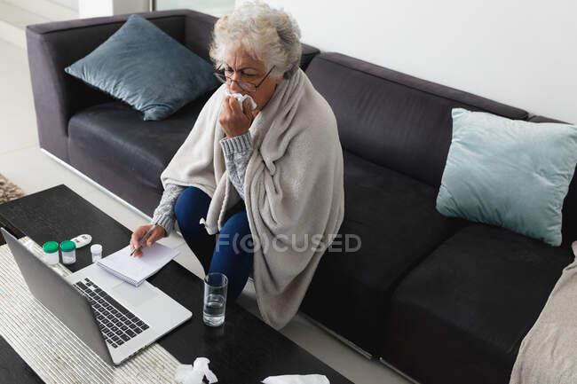 Змішана жінка, яка сидить на дивані, робить відео-дзвінок за допомогою ноутбука. Перебуваючи вдома в ізоляції під час карантину.. — стокове фото