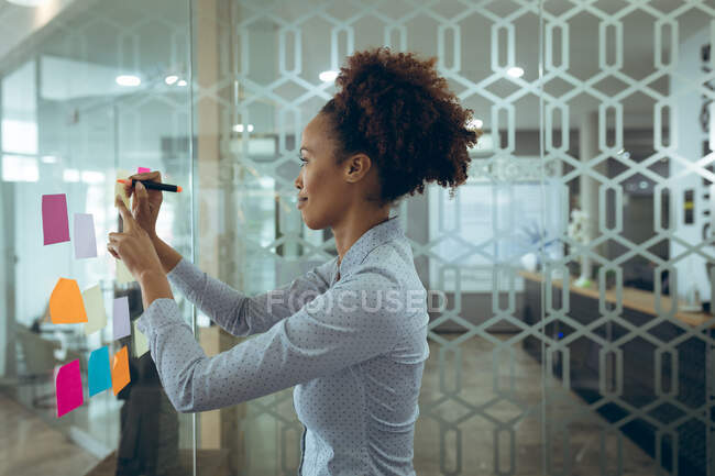 Mixed race businesswoman taking notes on glass board and thinking. work at an independent creative business. — Stock Photo