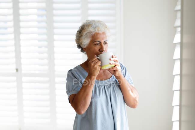 Mujer mayor de raza mixta bebiendo café junto a la ventana. permanecer en casa aislado durante el bloqueo de cuarentena. - foto de stock