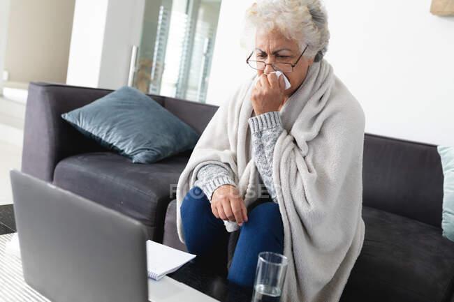 Mujer mayor de raza mixta sentada en un sofá haciendo videollamadas usando un portátil. permanecer en casa aislado durante el bloqueo de cuarentena. - foto de stock