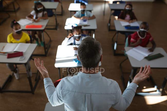 Vista trasera de la enseñanza masculina caucásica en la clase en la escuela. higiene y distanciamiento social en la escuela durante la pandemia de covid 19 - foto de stock