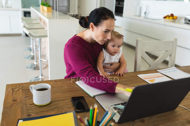 Mãe branca segurando seu bebê usando laptop enquanto trabalhava em casa. maternidade, amor e conceito de cuidado do bebê — Fotografia de Stock