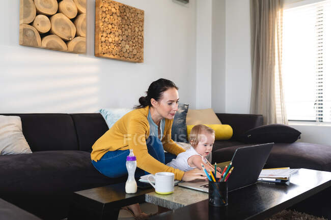 Caucasian mother holding her baby using laptop while working from home. motherhood, love and baby care concept — Stock Photo