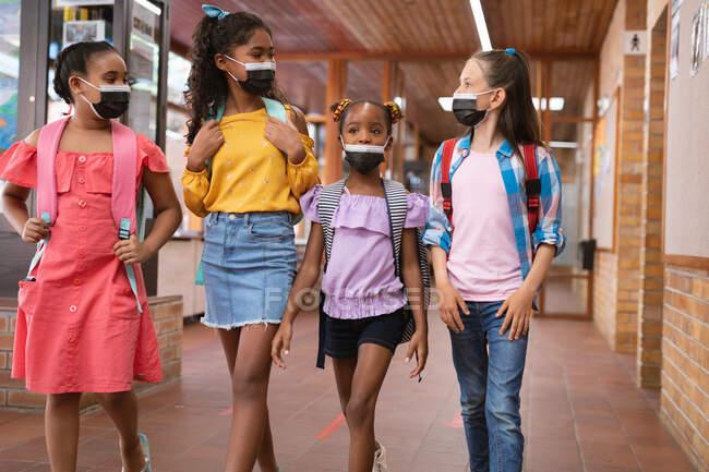 Grupo de diversos grupos de niñas que usan máscaras faciales mientras caminan en el pasillo de la escuela. higiene y distanciamiento social en la escuela durante la pandemia de covid 19 - foto de stock