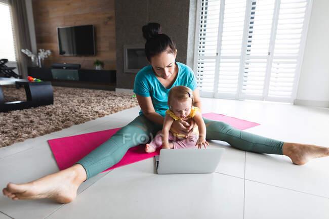 Кавказька мати тримає своє немовля, виконуючи розтягнуті вправи, дивлячись на ноутбук удома. материнство, любов і догляд дітей — стокове фото