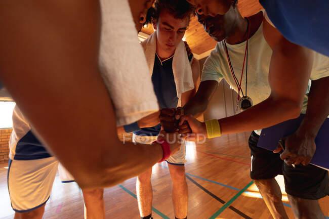 Equipo de baloncesto masculino diverso y entrenador en grupo formando equipo. baloncesto, entrenamiento deportivo en una cancha cubierta. - foto de stock