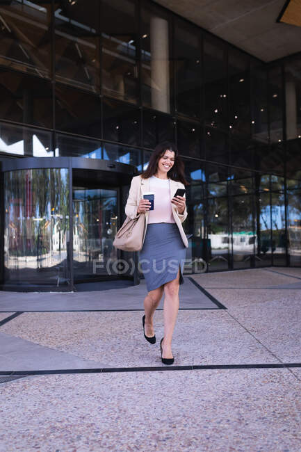 Caucasian businesswoman holding coffee cup smiling while using smartphone walking at corporate park. business and office concept — Photo de stock
