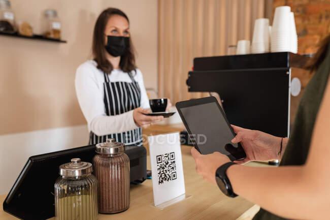 Cáucaso cliente femenino celebración de la tableta, escaneo de código qr, tomando la orden del propietario del negocio. pequeño negocio de café independiente durante coronavirus covid 19 pandemia. - foto de stock