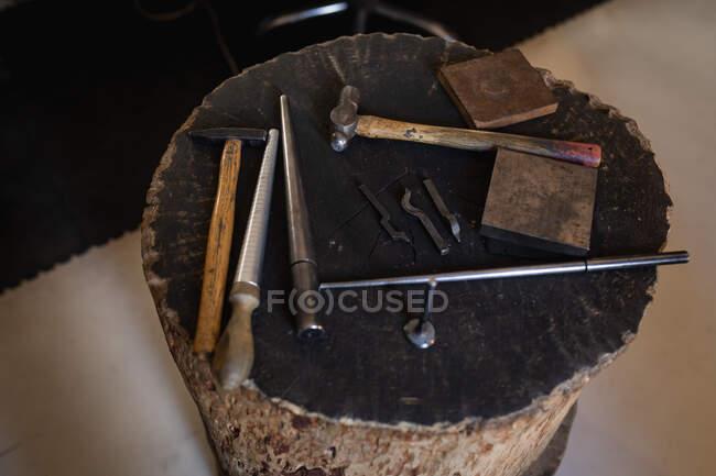 Різні інструменти для ювелірних виробів, молотки та файли лежать на столі в майстерні. Незалежний ремісничий бізнес. — стокове фото