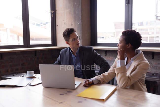 Empresário caucasiano e empresária afro-americana discutindo juntos enquanto estavam sentados em um café. conceito de negócio e trabalho remoto — Fotografia de Stock