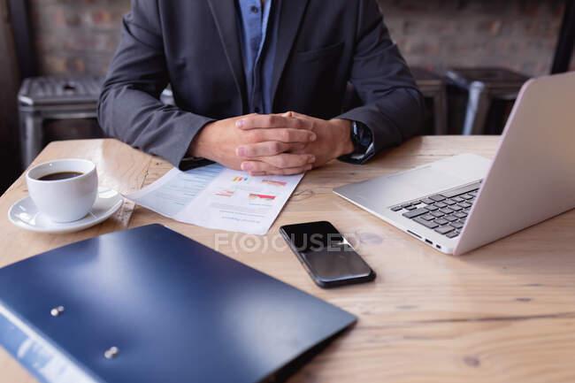 У середній частині бізнесмена сидять під час багаторазового офісного обладнання на столі в кафе. бізнес і концепція віддаленої роботи — стокове фото