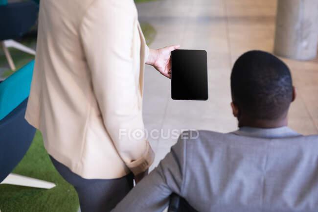 У секції ділової жінки, яка показує цифрову табличку інваліду-бізнесмену на інвалідному візку в офісі. концепція бізнесу та офісу — стокове фото