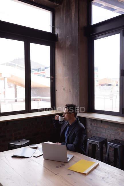 Hombre de negocios caucásico bebiendo café mientras mira por la ventana a un café. concepto de negocio y trabajo remoto - foto de stock