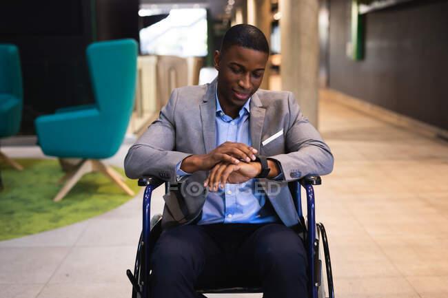 Неповносправний афроамериканський бізнесмен, який сидить на інвалідному візку в сучасному офісі. концепція бізнесу та офісу — стокове фото