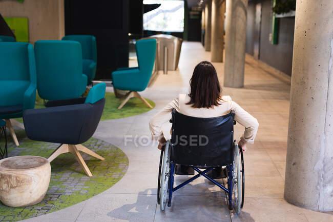 Передній вигляд інвалідної кавказької бізнесменки, яка сидить на інвалідному візку в сучасному офісі. концепція бізнесу та офісу — стокове фото