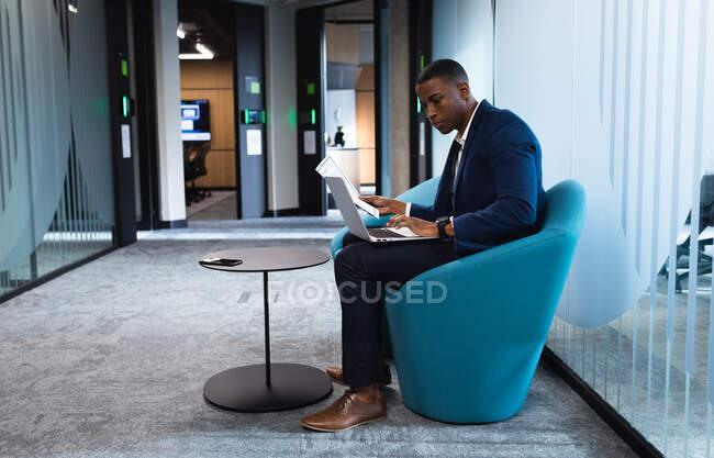 Африканський американський бізнесмен, який тримає документ за допомогою ноутбука, сидячи на стільці в сучасному офісі. концепція бізнесу та офісу — стокове фото