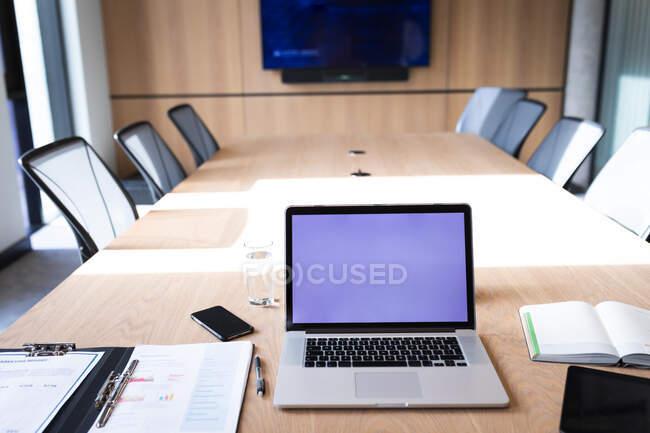 Vue de l'ordinateur portable et de l'équipement de bureau sur une table en bois dans la salle de réunion du bureau moderne. concept d'entreprise et de bureau — Photo de stock