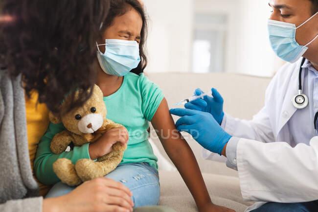 Médico masculino hispano que da la vacuna covid a la hija paciente con madre, usando máscaras faciales. servicios médicos y sanitarios durante la pandemia de coronavirus covid 19. - foto de stock