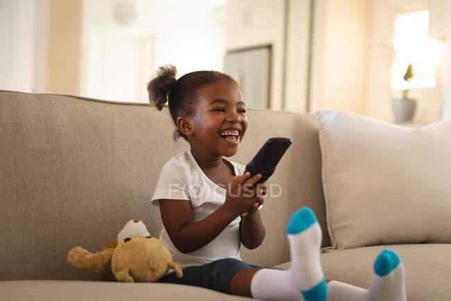 Una ragazza afroamericana che ride seduta sul divano con un orsacchiotto, che tiene il telecomando, guarda la TV. trascorrere del tempo libero a casa. — Foto stock