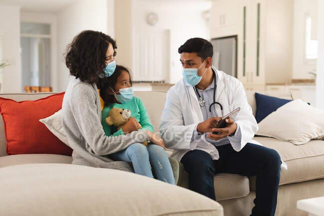 Médico masculino hispano usando tableta en casa de la madre y la hija paciente, todos con mascarillas. servicios médicos y sanitarios durante la pandemia de coronavirus covid 19. - foto de stock