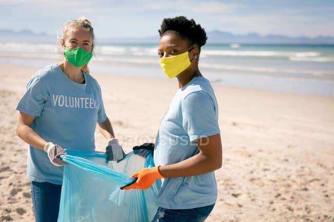 Duas mulheres diversas vestindo camisetas voluntárias e máscaras faciais pegando lixo da praia. voluntários de conservação ecológica, limpeza de praia durante coronavírus covid 19 pandemia. — Fotografia de Stock