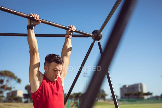 Homem musculoso caucasiano pendurado em quadro de exercício ao ar livre. estilo de vida ativo saudável, treinamento cruzado para fitness. — Fotografia de Stock